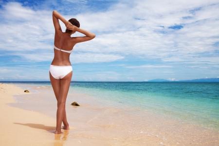 Gebräunt Frau zurück Relaxen am Sandstrand