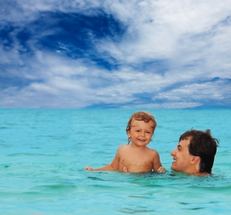 dad and his kid having fun in the water, swimming and laughing photo
