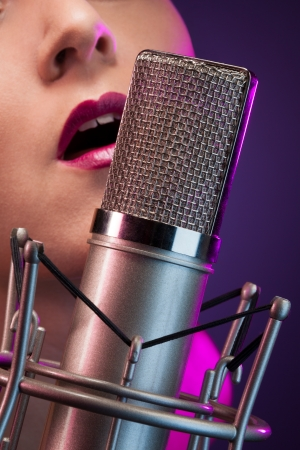 closeup of pretty woman singing in microphone on stage photo