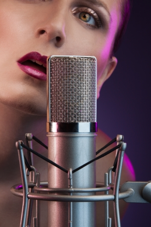 beautiful woman singing on the stage next to the microphone photo