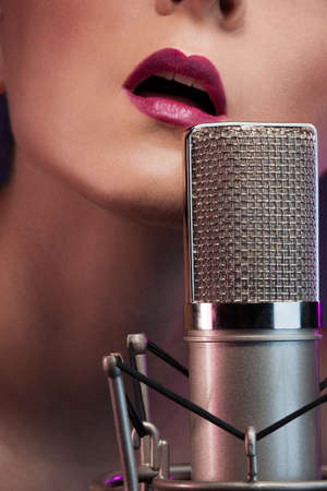 Pretty girl singing with microphone photo