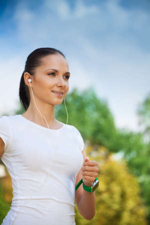 beautiful girl running in the park and listening to music with her headphones photo
