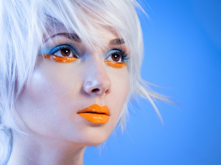 futuristic woman: close portrait of attractive blonde girl with sensual orange lips Stock Photo