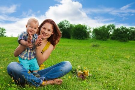 aplaudiendo: mamá aplausos con su bebé sentado en la hierba