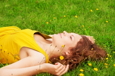 girl relaxing on the grass and looking up photo