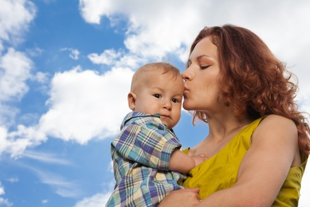 mother kissing her adorable baby on cloudy background photo