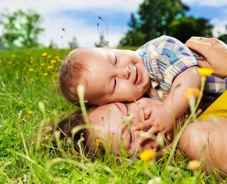 joven mam� y su beb� que pone en la hierba y abrazos photo