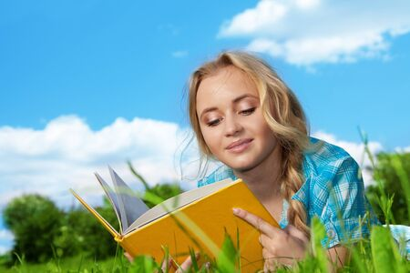 blonde girl laying on the green grass and reading photo