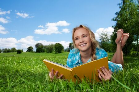 interested: blonde girl laying on the green lawn and reading and dreaming