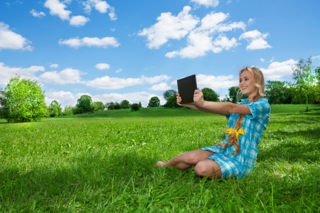 pretty smiling girl sitting on the green lawn and browsing internet using tablet pc photo