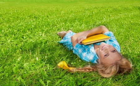 blonde nice girl laying on the green grass photo