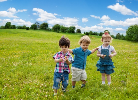 two boys and one girl walking in the park photo