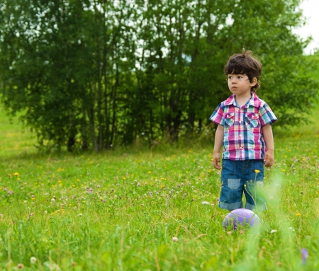 sad boy waiting friend in the park to play football Stock Photo