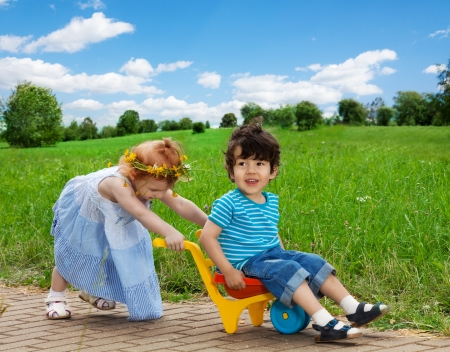 cute girl carrying her brother in the cart Stock Photo - 15865820