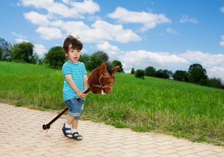 kid playing with horse stick pretending to be a cowboy