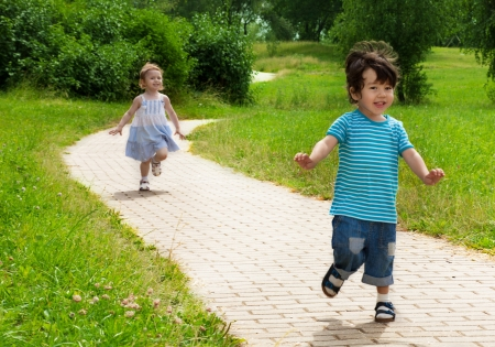pursue: little girl chasing cute little boy in the park Stock Photo