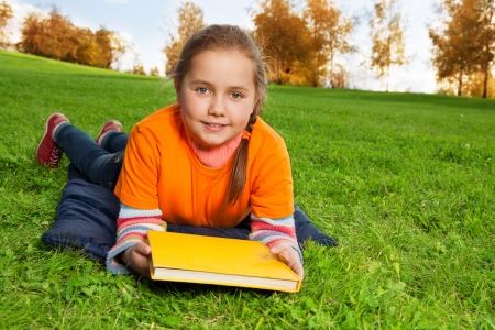 8 years: nice 8 years old girl laying in the autumn park Stock Photo