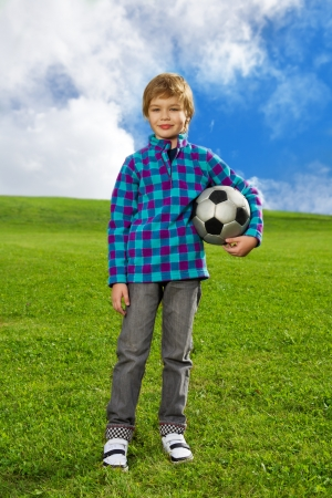 7 years old boy standing on the field with football ball photo