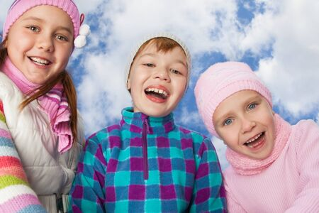 three laughing kids on sky background photo