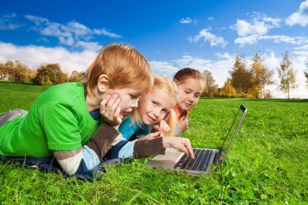 7 years old: bright kids laying with laptop in autumn park