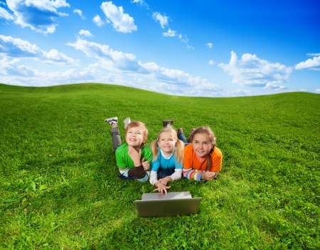 three cute kids laying with laptop on green grass in the park photo