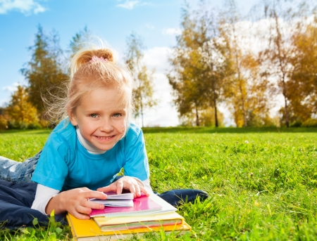 Cute smiling blonde girl in park laying on green grass in sunny weather photo