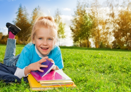 laughing little girl with books in park photo