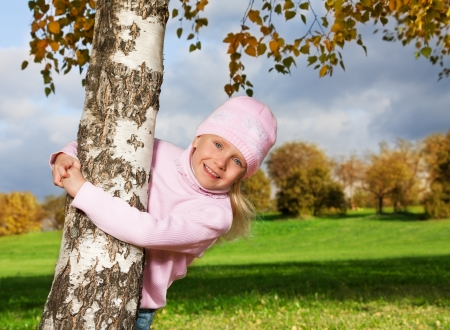 cute little girl in hat and sweater hugging autumn tree photo