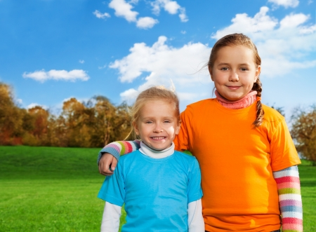 Happy sisters walking in autumn park photo
