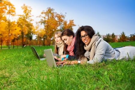 learning computer: tre studenti delle scuole superiori di posa con i portatili nel parco