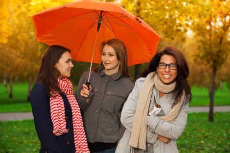 Three girls under one umbrella in the park photo