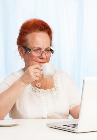 damas antiguas: Mujer mayor leyendo noticias de su computadora portátil en la mañana Foto de archivo