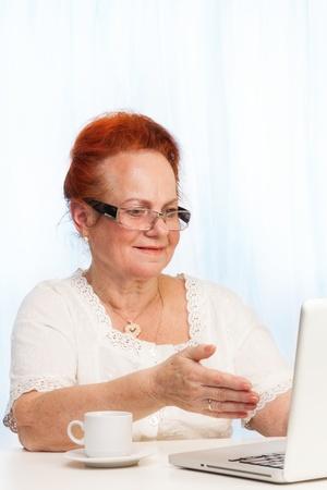 damas antiguas: mujer jubilada sentada y apuntando a la pantalla del portátil Foto de archivo