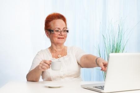 vejez feliz: positivo señora mayor sentada detrás del escritorio y apuntando a la pantalla del portátil Foto de archivo