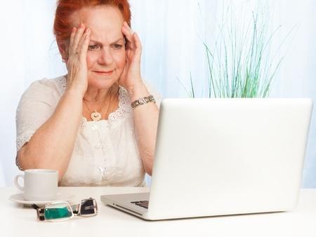 persona confundida: Mujer mayor con la expresión confusa en su cara sentado detrás de su computadora portátil