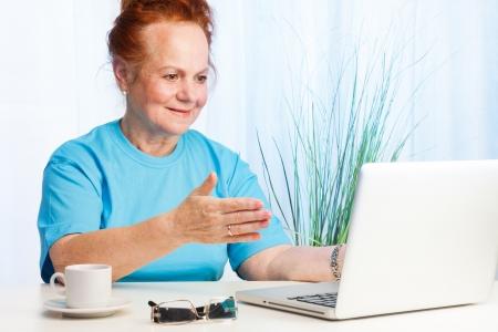 vejez feliz: Señora mayor sentada detrás de la mesa y apuntando a la pantalla