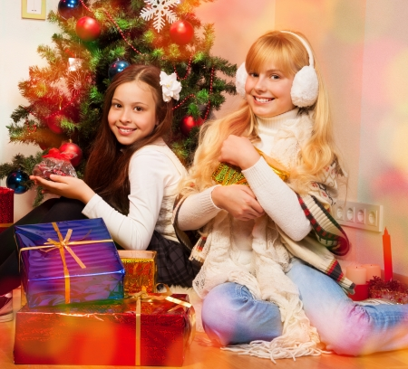 Two girls sitting near Christmas tree and holding their presents photo