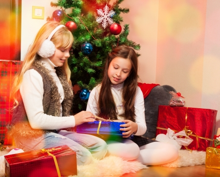 Friends giving presents each other sitting near christmas tree photo