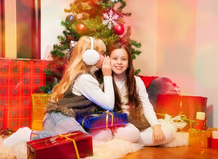 8 years old: Two 8 years old girls sharing each other secrets on Christmas Eve