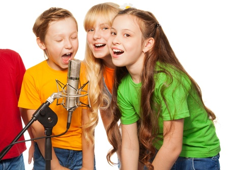 cantando: Los niños y las niñas que cantan en micrófono
