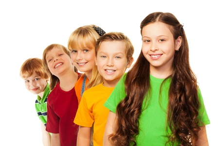 five years old: Five happy kids standing in a line each behind other, with natural smile and girl with long dark hairs in front