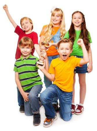 Zwycięski zespół pięciu osiem lat chłopców i dziewcząt z miska krzyczy i uśmiechnięty