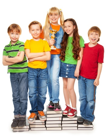 Girls and boys standing on books holding their award photo