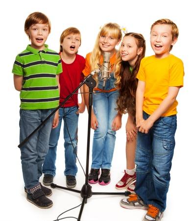 ni�os rubios: Grupo de ni�os cantando al micr�fono de pie juntos, aislado en blanco Foto de archivo