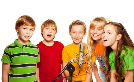 sings: Group of 5 happy 8 years old kids with microphone singing together Stock Photo