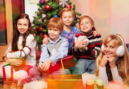 five cute kids sitting near Christmas tree ready to celebrate photo