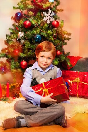 Cute boy sitting near Christmas tree holding present from Santa photo