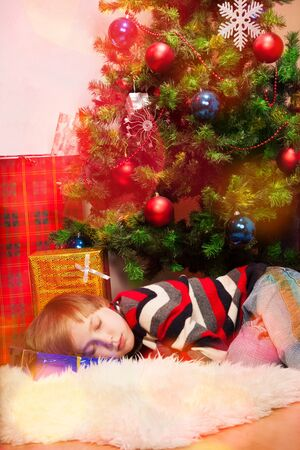 Little boy fell asleep under Christmas tree photo