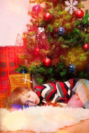 under tree: Little boy fell asleep under Christmas tree