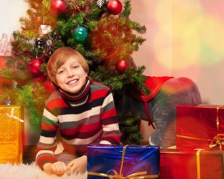 Cute little boy in New Year Eve waiting to open his presents photo